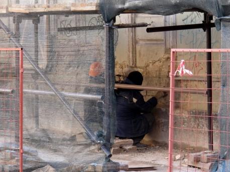 Рабочие крепят сетку на стену (2)